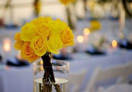 yellow roses in glass vase on beach